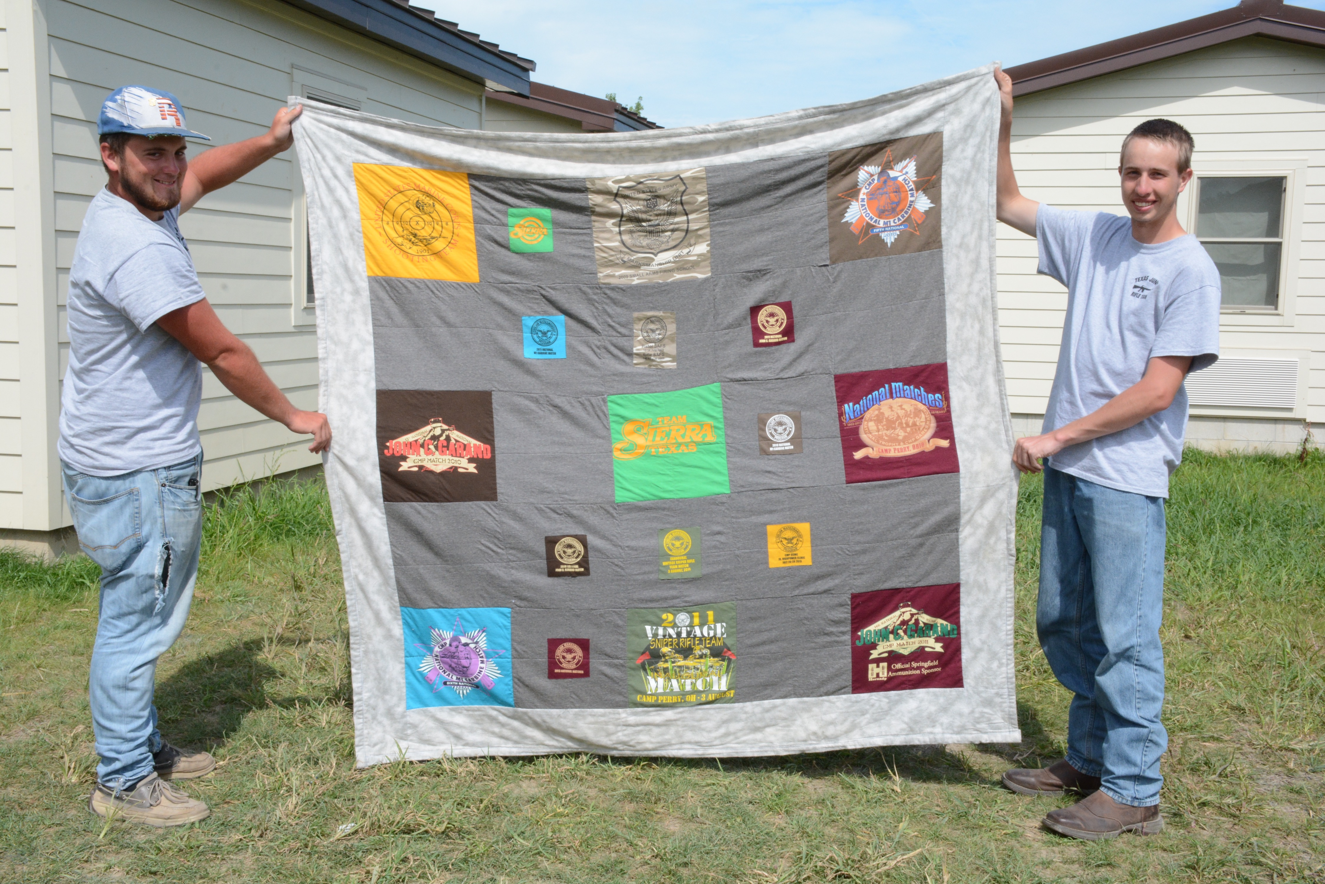 Eric McDaniels (right) holds a blanket covered with patches of old t-shirts he's acquired during his many trips to the National Matches. The blanket was a gift from his very talented and thoughtful grandmother. Teammate James Chesley (left) assists.