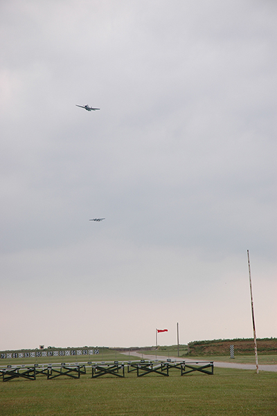 "A World War II torpedo bomber and B-25 made four passes over the Camp Perry ranges. The planes opened their bomb doors and ""dropped"" explosives onto the ground fleet below."